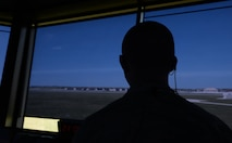Senior Airman Grant Krause, a 28th Operations Support Squadron air traffic control journeyman, looks at the flight line through blue shaded blinds inside the air traffic control tower at Ellsworth Air Force Base, S.D., July 10, 2018. Due to the high-stress nature of the job, the air traffic controller's technical training attrition rate is only 50 percent, making the success of their job even more crucial. (U.S. Air Force photo by Airman 1st Class Nicolas Z. Erwin)