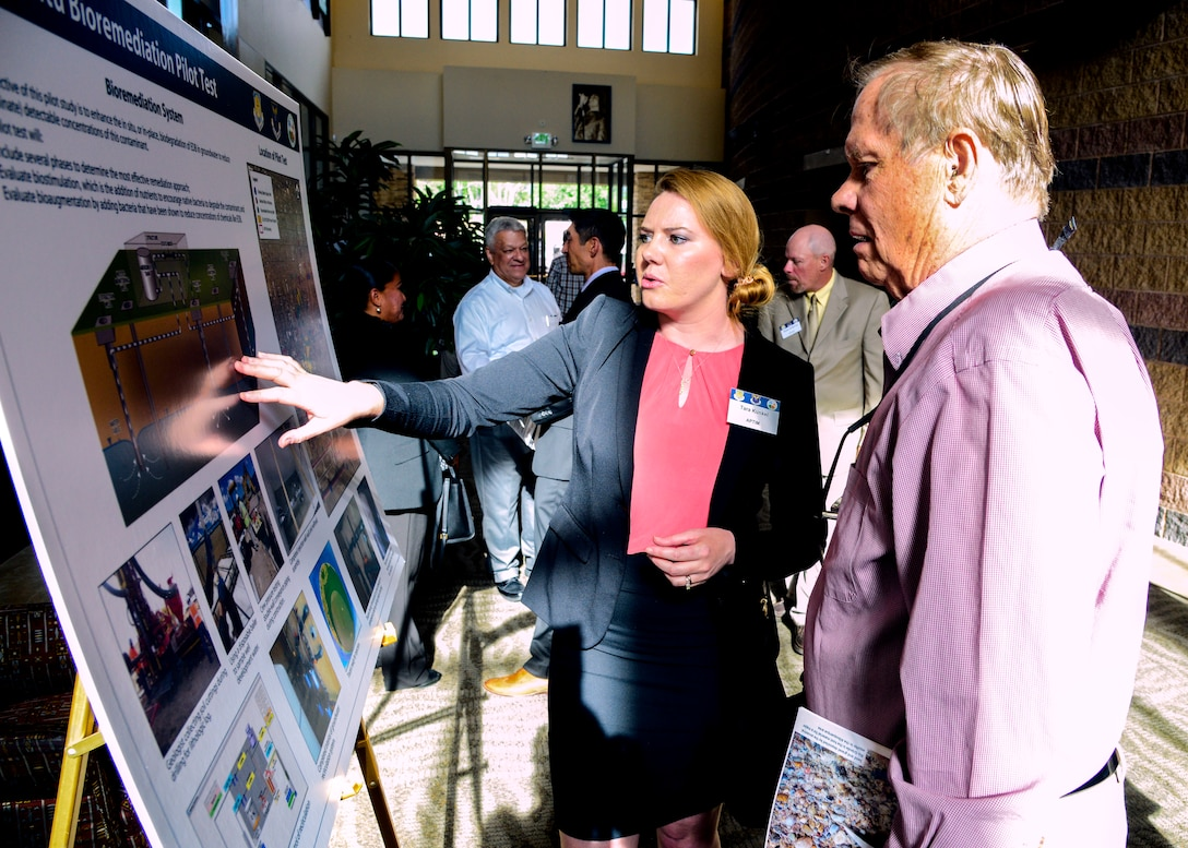Tara Kunkel, APTIM, discusses Kirtland Bulk Fuels Facility remediation data with Dr. Eric Nutall during the poster session preceding the BFF Public Meeting July 12 at the African American Performing Arts Center. The quarterly meeting was held to bring people up to date on remediation efforts and related data. (U.S. Air Force photo by Jim Fisher)