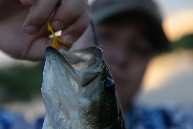 Airman John Ennis, a 28th Bomb Wing Public Affairs broadcast journalist, unhooks a bass caught at Gateway Lake on Ellsworth Air Force Base, S.D., July 12, 2018. Fish in the lakes include, but are not limited to, largemouth bass, rainbow trout, bluegill, perch, crappie, green sunfish and red sunfish. (U.S. Air Force photo by Airman 1st Class Nicolas Z. Erwin)