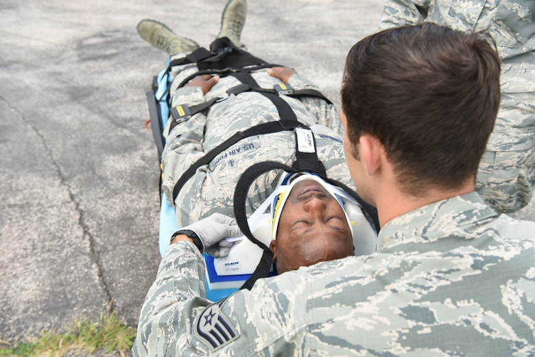 Staff Sgt. Michael Glowth, a 28th Medical Group aerospace medical technician, practices placing head blockers on Tech. Sgt. Ricky Dunbar, the noncommissioned officer in charge of the ambulance services flight at Ellsworth Air Force Base, S.D., July 10, 2018. Aerospace medical technicians go through a 98-day course that prepares them for the stresses and responsibilities of serving in ambulance services. (U.S. Air Force photo by Airman 1st Class Thomas Karol)