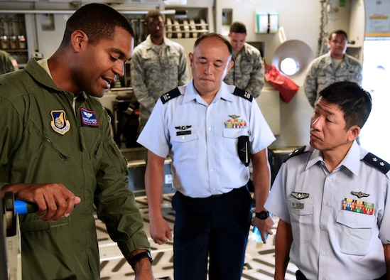 U.S. Air Force Capt. Warren Carter, Operations Element Chief, 18th Aeromedical Evacuation Squadron, Det 1, speaks with Koku Jieitai, Japan Air Self Defense Force, Maj. Gen. Shinya Bekku, Koku Jieitai Surgeon General, aboard a C-17 Globemaster III at Joint Base Pearl Harbor-Hickam, Hawaii, July 11, 2018.