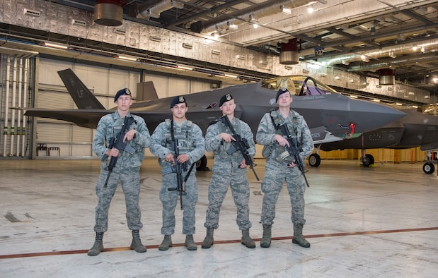 (From left to right) Senior Airman Daniel Karcher 423rd Security Forces Squadron, Senior Airman Lucas Reichenberger, 423rd SFS, Airman 1st Class Victor Williams, 422nd SFS and Airman 1st Class Jaxon Ramsey, 422nd SFS, stand guard over F-35A Lightning II Joint Strike Fighters during the Royal International Air Tattoo at RAF Fairford, July 14, 2018. This year's RIAT celebrated the 100th anniversary of the Royal Air Force and highlighted the United States' ever-strong alliance with the U.K. (U.S. Air Force photo by Senior Airman Chase Sousa)