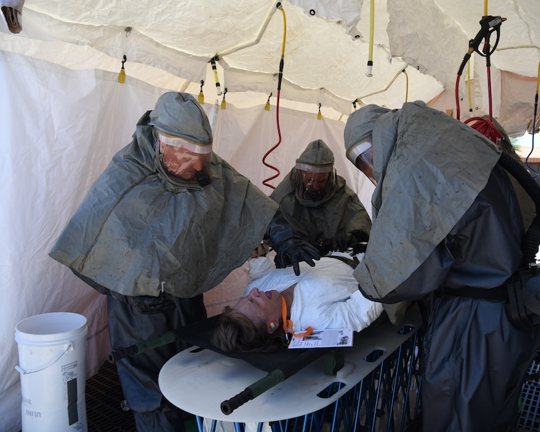 through an In-Place Patient Decontamination station during an exercise at the Goldwater Air National Guard Base, May 22. The purpose of the exercise was to train and evaluate the IPPD team's ability to decontaminate and prepare a patient to be transported onto a higher level of medical care. (U.S. National Guard photo by Staff Sgt. Wes Parrell)