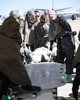 Members of the 161st Air Refueling Wing receive a patient to process through an In-Place Patient Decontamination station during an exercise at the Goldwater Air National Guard Base, May 22. The purpose of the exercise was to train and evaluate the IPPD team's ability to decontaminate and prepare a patient to be transported onto a higher level of medical care. (U.S. Air National Guard photo by Staff Sgt. Wes Parrell)