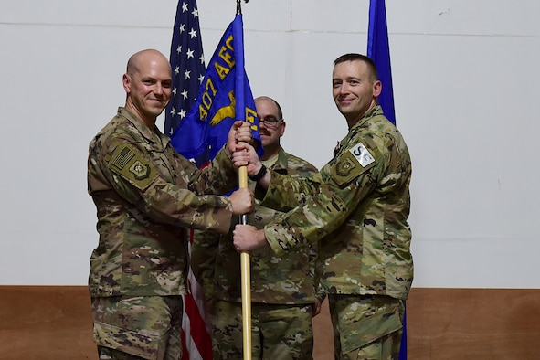 Two Airmen hold on to a squadron flag