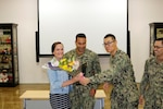 Navy Chief Petty Officer Yu He presents flowers to Molly Rivera at the Ombudsman induction.