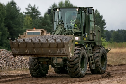 Sgt. Zac Hartley, a horizontal construction engineer in the West Virginia Army National Guard, assigned to 812th Engineer Company, 1092nd Engineer Battalion, 111th Engineer Brigade based out of Eleanor, West Virginia, operates a front end loader to place gravel at Drawsko Pomorskie Training Area, Poland, during Resolute Castle, July 12, 2018.