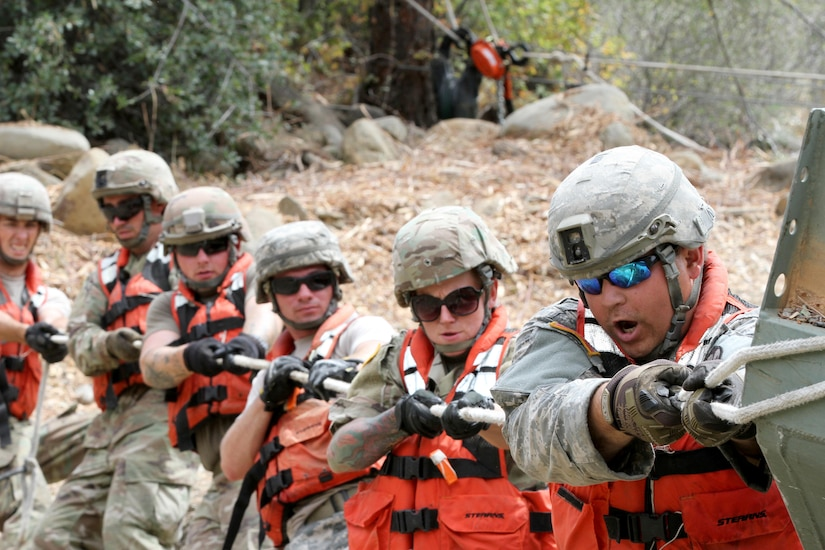A row of service members pull on a rope.