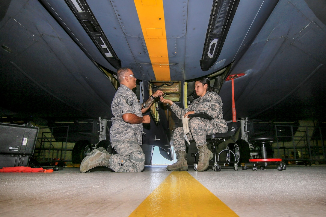 Airmen remove an antenna from a KC-135R Stratotanker.