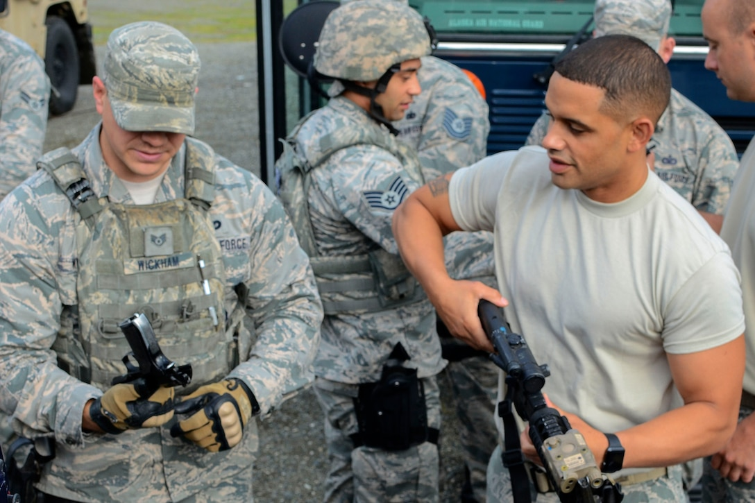 An airman retrieves a weapon from a team member before a combat patrol exercise.