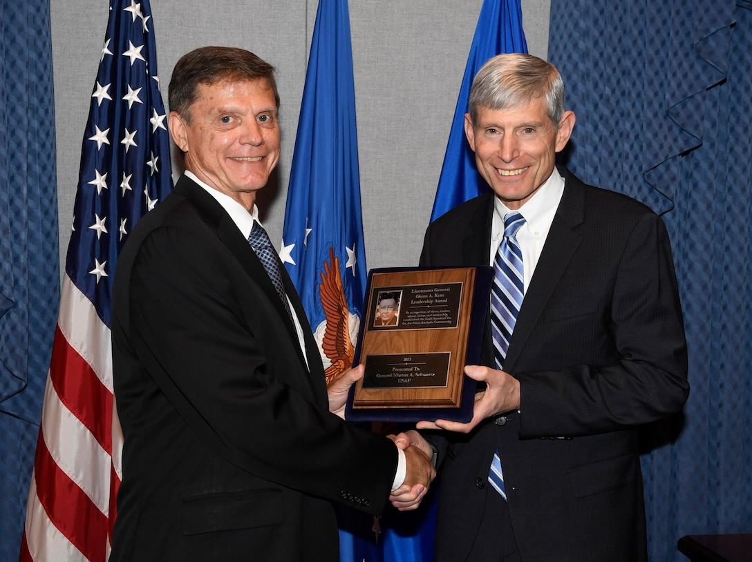 Former Chief of Staff of the Air Force General Norton Schwartz is presented the Lt. Gen. Glenn A. Kent Leadership Award by Kevin Williams, director of Air Force Studies, Analysis and Assessments during a ceremony in the Pentagon, Washington, DC, July 13, 2018. Schwartz served as CSAF from 2008 to 2012.