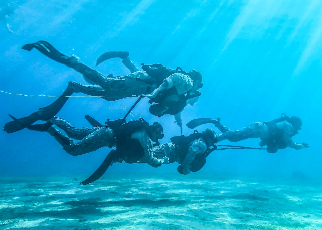 U.S. Marines with Maritime Raid Force (MRF), 26th Marine Expeditionary Unit (MEU), swim underwater during dive training in Aqaba, Jordan, July 8, 2018. Iwo Jima is deployed to the U.S. 5th Fleet area of operations in support of naval operations to ensure maritime stability and security in the central region, connecting the Mediterranean and the Pacific through the western Indian Ocean and three strategic choke points. (U.S. Marine Corps photo by Cpl. Jon Sosner/Released)