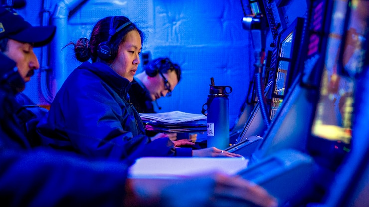 A row of sailors sit in front of consoles.