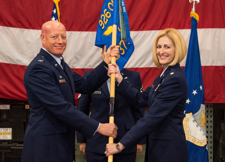 Col. Todd Tobergte, 926th Operations Group commander, passes the 379th Space Range Squadron guidon to Lt. Col. Sheila Wilds as she assumes command of the squadron during a ceremony July 14th, 2018.