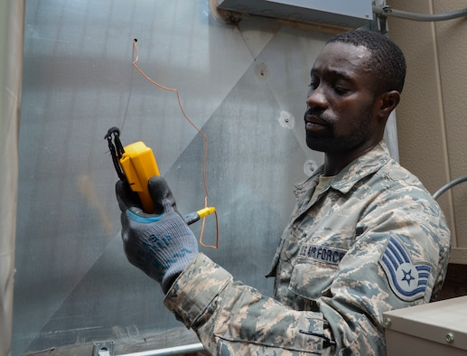 Staff Sgt. Cheick Kamagate, Heating, Ventilation, Air Conditioning/Refrigeration and Control technician assigned to the 512th Civil Engineer Squadron Reserve Unit at Dover Air Force Base, Delaware checks the air supply temperature going into a 57th maintenance facility on Nellis Air Force Base. The 99th CES HVAC shop has prepared for the summer heat by utilizing over 50 Air Reserve Component technicians across 13 other bases. (U.S. Air Force photo by Airman Bailee A. Darbasie)