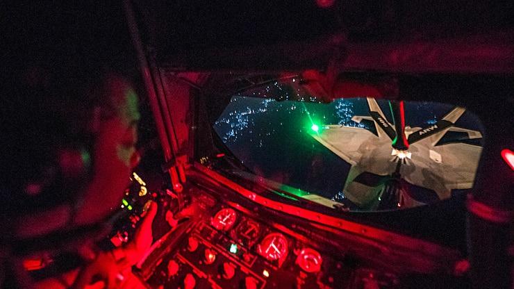 An airman looks out a window toward an aircraft in flight.