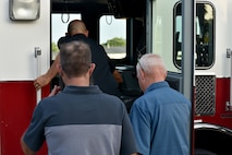 Nathan Garland, Clayton Garland and Louis Garland, decedents of late Chief Warrant Officer Louis F. Garland, board a firetruck to tour Goodfellow Air Force Base, Texas, July 13, 2018. The Garlands traveled from the Norma Brown building to the Louis F. Garland Department of Defense Fire Academy on a firetruck. (U.S. Air Force photo by Senior Airman Randall Moose/Released)