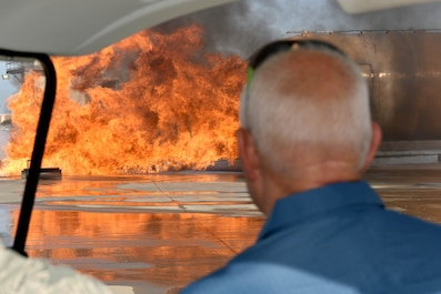 Louis Garland, son of late Chief Warrant Officer Louis F. Garland, watches a simulated plane fire in the Louis F. Garland Department of Defense Fire Academy on Goodfellow Air Force Base, Texas, July 13, 2018. According to Garland, the fire simulators on Goodfellow are much larger than the ones previously used on Chanute Air Force Base, the previous home of the fire academy before Goodfellow. (U.S. Air Force photo by Senior Airman Randall Moose/Released)