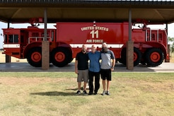 Clayton Garland, Louis Garland and Nathan Garland, decedents of late Chief Warrant Officer Louis F. Garland, pose before a P-15 Mammoth at the Department of Defense Fallen Firefighter Memorial on Goodfellow Air Force Base, Texas, July 13, 2018. The memorial houses firefighting equipment from the past and stands to honor military and DoD firefighters who died in the line of duty. (U.S. Air Force photo by Senior Airman Randall Moose/Released)