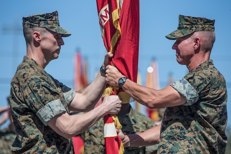 U.S. Marine Corps Maj. Gen. Robert F. Castellvi, left, the incoming commanding general of 1st Marine Division, recieves the division colors from Maj. Gen. Eric M. Smith, the outgoing commanding general, during a change of command ceremony held at Marine Corps Base Camp Pendleton, Calif., July 6, 2018.