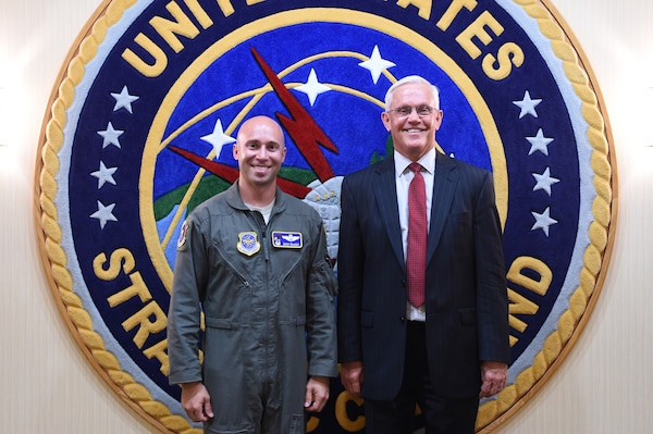 U.S. Air Force Lt. Col. Daniel McVay (left), 22nd Operations Support Squadron commander, is greeted by his father Patrick McVay, director of U.S. Strategic Command's (USSTRATCOM) Joint Exercise, Training and Assessments Directorate, at Offutt Air Force Base, Neb., July 10, 2018. Daniel McVay attended USSTRATCOM's Nuclear Commanders Course (NCC) from July 12 – 13, 2018. NCC is a two-day course designed to provide new nuclear enterprise commanders with a foundational understanding of USSTRATCOM's role in building and maintaining the nuclear war plan, nuclear command and control capabilities, and their unit's role in the strategic deterrence mission. USSTRATCOM has global responsibilities assigned through the Unified Command Plan that include strategic deterrence, nuclear operations, space operations, joint electromagnetic spectrum operations, global strike, missile defense, and analysis and targeting.