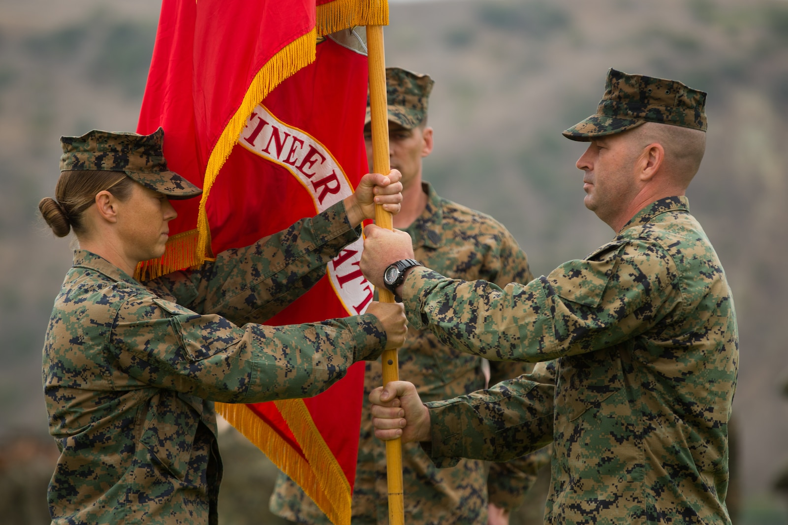 U.S. Marine Corps Lt. Col. Michelle I. Macander, left, incoming commanding officer of 1st Combat Engineer Battalion (CEB), 1st Marine Division, receives the colors from Lt. Col. Christopher M. Haar, offgoing commanding officer of 1st CEB, during a change of command ceremony at Marine Corps Base Camp Pendleton, Calif., June 22, 2018.