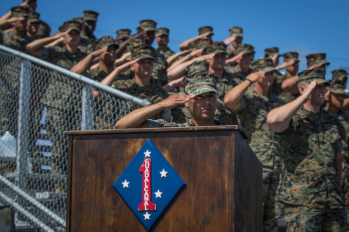 U.S. Marines with Headquarters Battalion (HQBN), 1st Marine Division (MARDIV), salute the American flag during a change of command ceremony at Marine Corps Base Camp Pendleton, Calif., June 19, 2018.