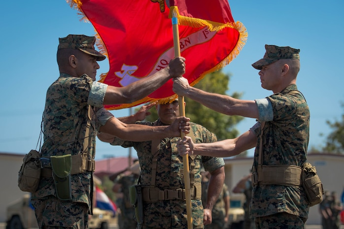 U.S. Marine Corps Maj. Arun Shankar, left, the incoming commanding officer of Headquarters Battalion (HQBN), 1st Marine Division (MARDIV), receives the Marine Corps flag from Col. Carlos O. Urbina, right, offgoing commanding officer of HQBN, 1st MARDIV, during a change of command ceremony at Marine Corps Base Camp Pendleton, Calif., June 19, 2018.