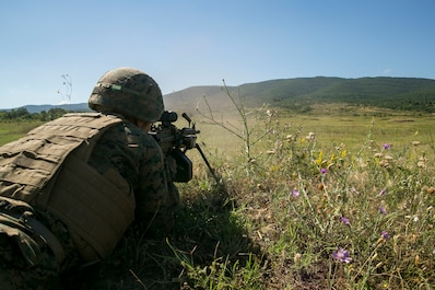 A U.S. Marine with Black Sea Rotational Force 18.1 engages a target using an M249 light machine gun during a deployment for training exercise at Novo Selo Training Area, Bulgaria, July 1, 2018.