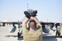 a airman uses hand signals to motion to a jet to stop moving