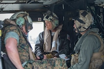 The Honorable Phyllis L. Bayer, center, Assistant Secretary of the Navy – Energy, Installations and Environment, Major General Vincent A. Coglianese, left, commander, Marine Corps Installations Command, and Sergeant Dallas Hodges, crew chief, Marine Light Attack Helicopter Squadron 369, 3rd Marine Aircraft Wing, prepare for take off in a UH-1Y Venom Helicopter during her visit to Marine Corps Base Camp Pendleton, California, July 16, 2018.