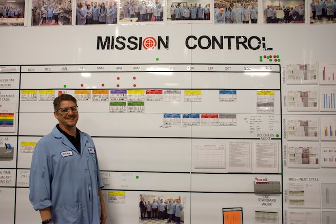 """Brian Roush, the Enersys operating system manager, poses for a photo next to the Enersys """"mission control"""" board July 12, 2018, in Warrensburg, Mo. Roush has been the primary point of contact in establishing a partnership with the 442d Fighter Wing in an effort to further continuous process improvement training at the wing. (U.S. Air Force photo by Senior Airman Taylor Davis)"""