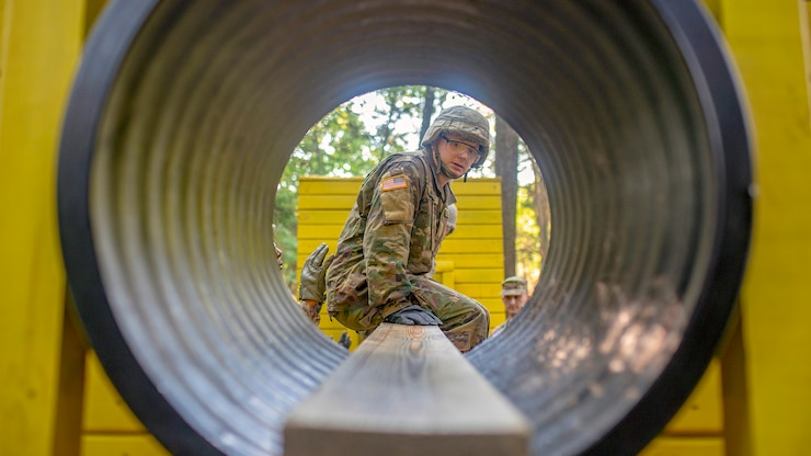 A soldier sits on a plank of wood looking through tunnel.