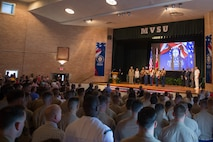 Loved ones, community members and distinguished visitors stand for the national anthem in the Mississippi Valley State University auditorium to honor the sacrifice of the fallen passengers and crew of Yanky 72, during the Memorial Ceremony, July 14, 2018. The Yanky 72 Memorial Ceremony was held to remember and honor the ultimate sacrifices made by the fallen Marines and Sailor of VMGR-452 and Marine Corps Special Operations Command. (U.S. Marine Corps photo by Lance Cpl. Samantha Schwoch/released)