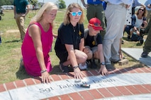 Family members pose next to the name of late Marine Sgt. Talon R. Leach, on a marble monument honoring the fallen Marines and sailor, lost in a 2017 plane crash near Itta Bena, Miss., Jul 14, 2018. More than 200 relatives and friends of the 16 people who died aboard the flight with the call sign Yanky 72, joined by countless county residents and military supporters at the ceremonies on campus of Mississippi Valley State University and across the street. (U.S. Marine Corps photo by Lance Cpl. Samantha Schwoch/released)