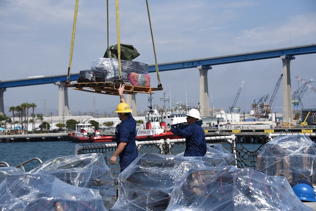 Crew members from the Coast Guard Cutter Steadfast send off a pallet of seized cocaine