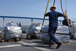 A U.S. Coast Guardsman prepares a pallet of seized cocaine to be offloaded