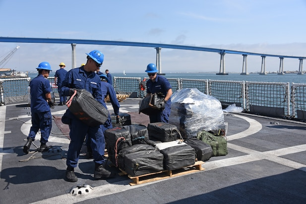 Crew members from the Coast Guard Cutter Steadfast load a pallet of seized cocaine