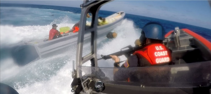 A U.S. Coast Guardsman aboard an interceptor boat pursues a suspected smuggling vessel