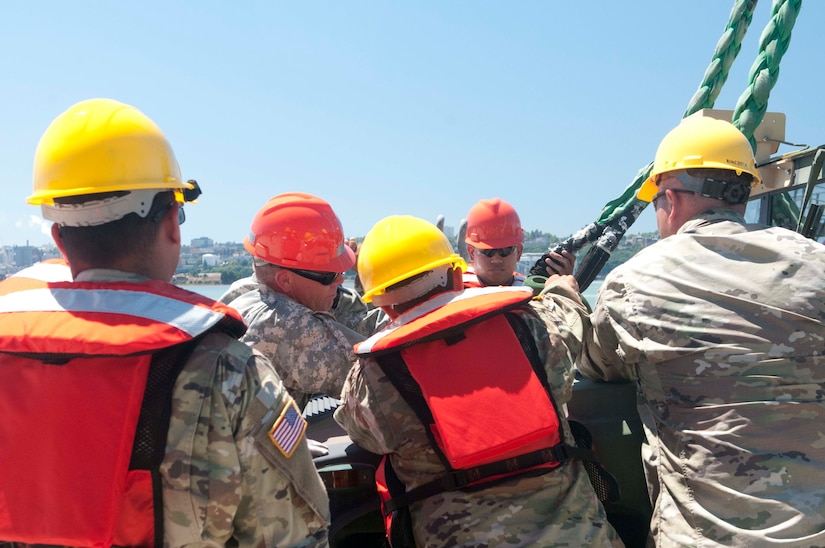Army watercraft operators prepare to load vehicles.