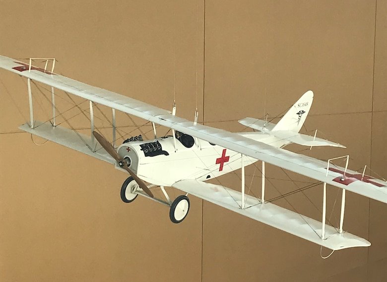 "A model of a ""Jenny"", a Curtiss JN-4, hangs above the atrium in USAFSAM. The ""Jenny"" was the first aircraft deemed as the first air ambulance. At the end of World War I, the United States Army recognized the need to air transport wounded soldiers. In 1918 Maj. Nelson E. Driver and Capt. William C. Ocker modified a Curtiss JN-4 ""Jenny"" bi-plane to accommodate a stretcher in order to transport patients. (U.S. Air Force Photo/Stacey Geiger)"