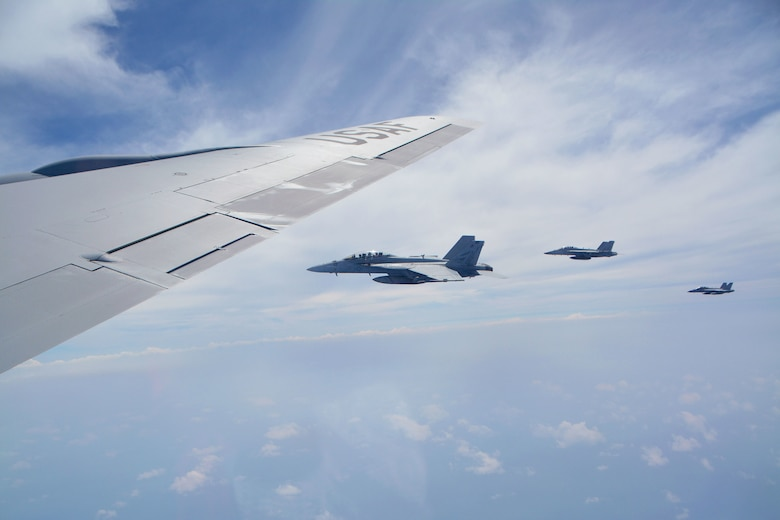 Three U.S. Navy F/A-18 Super Hornets from Carrier Air Wing Two, assigned to the aircraft carrier USS Carl Vinson (CVN 70), fly over the Pacific Ocean alongside a 507th Air Refueling Wing KC-135R Stratotanker from Tinker Air Force Base, Oklahoma, while participating in the Rim of the Pacific (RIMPAC) exercise, July 10. Twenty-five nations, 46 ships, five submarines, and about 200 aircraft and 25,000 personnel are participating in RIMPAC from June 27 to Aug. 2 in and around the Hawaiian Islands and Southern California. The world's largest international maritime exercise, RIMPAC provides a unique training opportunity while fostering and sustaining cooperative relationships among participants critical to ensuring the safety of sea lanes and security of the world's oceans. RIMPAC 2018 is the 26th exercise in the series that began in 1971. (U.S. Air Force photo by Tech. Sgt. Samantha Mathison)