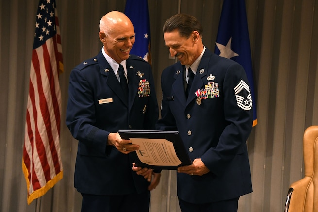 """Chief Master Sgt. Robert L. Walter, 94th Force Support Squadron superintendent, receives a certificate from Brig. Gen. Richard L. Kemble, 94th Airlift Wing commander, during a retirement ceremony held here July 14. """"Saying thanks for the last 36 years is just not enough, but I hope that I've worked with you long enough that I passed something along somewhere along the way,"""" Walter said. (U.S. Air Force photo/Senior Airman Josh Kincaid)"""