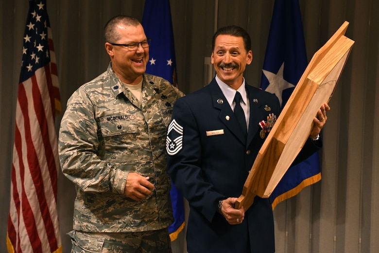 Chief Master Sgt. Robert L. Walter, 94th Force Support Squadron superintendent, smiles upon receiving a shadow box during his retirement ceremony held here July 14, 2018. Walter retired after 36 years of service in the active-duty Air Force, Air National Guard and, most recently, the Air Force Reserve. (U.S. Air Force photo/Senior Airman Josh Kincaid)