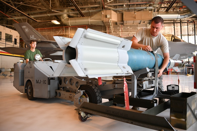 Staff Sgt. Andrew Rapp (right) and Senior Airman Connor Hansen, 419th Aircraft Maintenance Squadron, prepare to load a weapon onto an F-35 Lightning II during a friendly competition July 6 at Hill Air Force Base, Utah