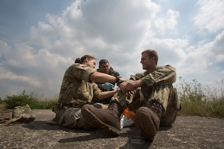 Petty Officer 2nd Class Michael S. Robelo, a hospital corpsman with 2nd Air Naval Gunfire Liaison Company assists Maj. Angela Servis, a medical officer with 29th Commando Royal Artillery, while providing notional medical aid to a British soldier during Exercise Green Cannon at Salisbury Plains, United Kingdom, July 6, 2018. (U.S. Marine Corps photo by Cpl. David Delgadillo)