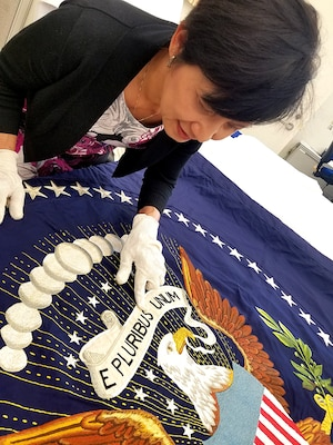 DLA Troop Support Clothing and Textiles embroidery specialist Linda Le inspects the only 49-star presidential flag made during a visit from presidential flag collectors Chuck and Donna Douglas in late June in Philadelphia. DLA embroiders are the sole authorized producers of the current 50-star presidential and vice presidential flags.