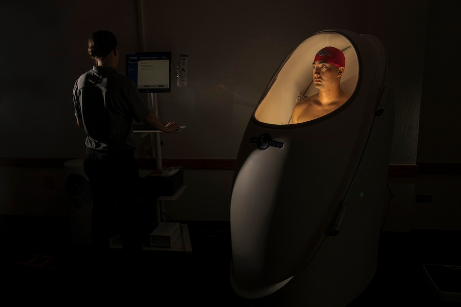An airman stands in a lighted pod during a body composition test.