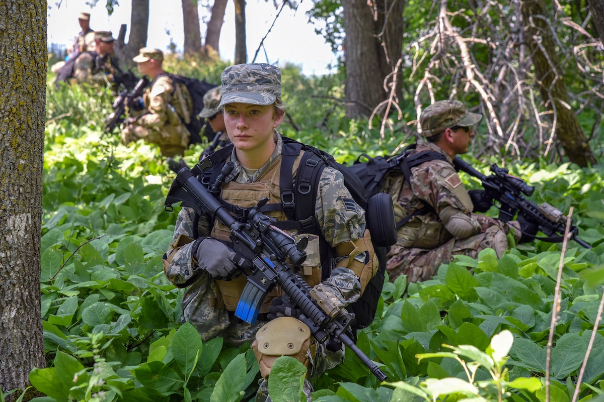 Airmen walk through a wooded area with weapons.