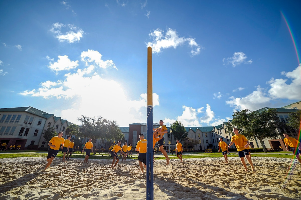 Sailors play volleyball near buildings.